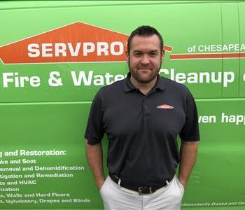 male office employee in front of green vehicle