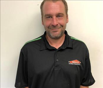 male office employee with black SERVPRO polo on