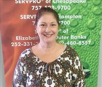 female office employee in front of SERVPRO sign