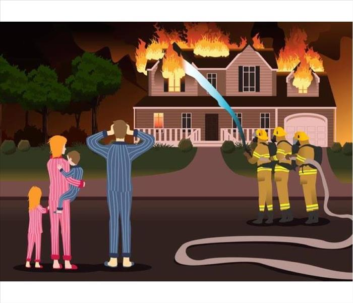 A family standing outside of the house that is on fire.